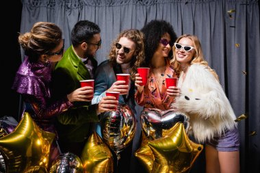 Happy interracial friends in sunglasses celebrating with plastic cups near grey curtain on black background stock vector