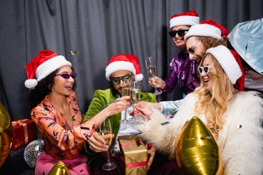 Happy interracial friends in santa hats and sunglasses clinking with glasses on grey couch on grey background stock vector