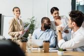schwangere afrikanisch-amerikanische Geschäftsfrau hält digitales Tablet in der Nähe glücklicher multiethnischer Mitarbeiter
