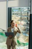 verträumte Geschäftsfrau hält Laptop in der Hand, während sie im Büro durch Fenster wegschaut