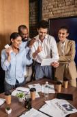 vzrušený multikulturní podnikatelé prokazující úspěch gesto poblíž kolegy s digitálním tabletem