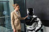 radostná podnikatelka stojící poblíž robota v kanceláři