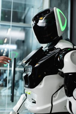 Ofiste kadın eli, insansı robotun yanında.