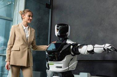 Mutlu iş kadını ofiste insansı robota dokunuyor.