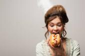 mladá žena v retro oblečení kousání lahodné hot dog izolované na šedé