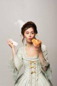 užaslý, retro styl žena drží hot dog a papírový ubrousek izolované na šedé