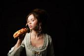 hezká žena v elegantních retro šaty drží lahodný hot dog izolované na černé