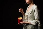 abgeschnittene Ansicht einer eleganten Frau im Vintage-Kleid mit Pommes frites isoliert auf schwarz