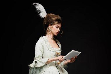 Siyah üzerine izole edilmiş dijital tablet kullanan zarif, klasik elbiseli genç bir kadın.