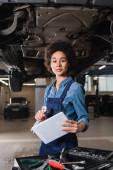 jistý mladý africký americký mechanik stojící pod autem a držící digitální tablet v garáži