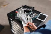 részleges kilátás fiatal szerelő visel kesztyű kéznél közelében szerszámosláda és digitális tabletta a garázsban