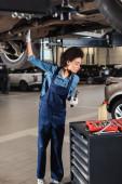mladý africký americký mechanik pracující pod autem v garáži