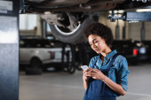 young african american mechanic holding cellphone in hands in garage