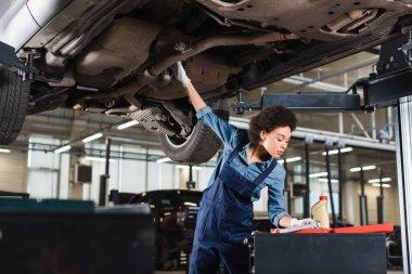 Young african american mechanic in overalls repairing bottom of car in garage stock vector