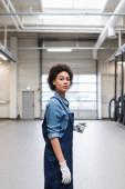 sebevědomý mladý africký americký mechanik v rukavicích stojící a při pohledu na kameru v garáži