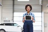 usmívající se mladý africký americký mechanik zobrazující digitální tablet s prázdnou obrazovkou a při pohledu na kameru v garáži