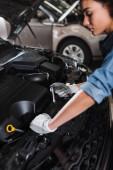 mladý africký americký mechanik držení klíč upevnění motor v autě s otevřenou kapotou v garáži