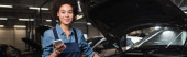 usmívající se mladý africký americký mechanik stojící s mobilem u auta s otevřenou kapotou v garáži, banner