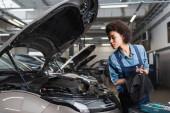 fiatal afro-amerikai szerelő szárító kéz törülköző közelében autó nyitott motorháztető a garázsban