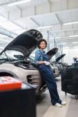 mladý africký americký mechanik stojící v blízkosti aut s otevřenou kápí v auto opravy