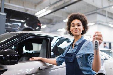 gülümseyen Afro-Amerikan tamirci tulumuyla garajda arabanın yanında anahtar tutuyor.