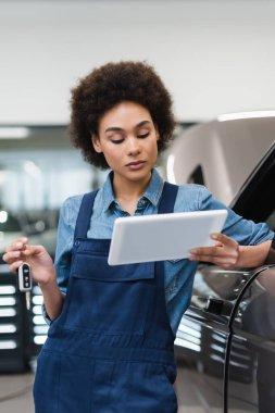 Genç Afrikalı Amerikalı tamirci arabanın anahtarını tutuyor ve garajdaki dijital tablete bakıyor.