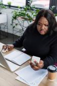 africký Američan plus velikost businesswoman při pohledu na smartphone v blízkosti monitoru počítače v kanceláři