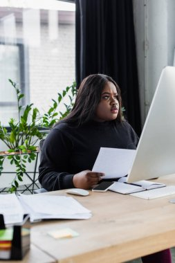 Concentrated african american plus size businesswoman looking at computer monitor in office stock vector