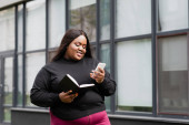 cheerful african american plus size woman holding notebook and smartphone outside