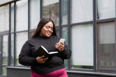 Neşeli Afro-Amerikan artı uzun boylu kadın dışarıda defter ve akıllı telefon tutuyor.