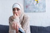 napjatá arabka v hidžábu sledující doma film