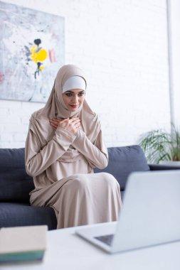 Müslüman kadın dizüstü bilgisayardaki video görüşmesi sırasında minnet jesti gösteriyor.