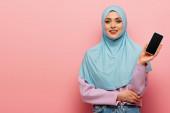 hübsche arabische Frau lächelt in die Kamera, während sie Handy mit leerem Bildschirm auf rosa Hintergrund zeigt