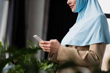 Ofiste cep telefonuyla sohbet eden tesettürlü Arap iş kadını görüntüsü