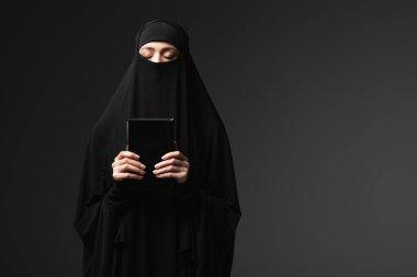 Muslim woman holding koran while praying isolated on black stock vector