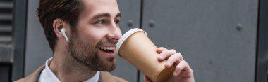 Happy businessman in earphones drinking coffee to go near building, banner stock vector