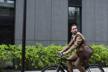 bearded businessman in earphones riding bicycle near building