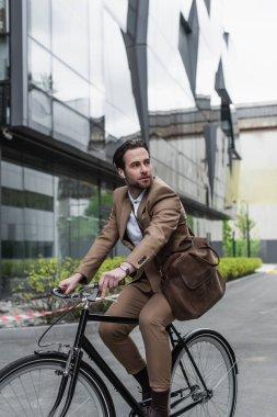 Binaya yakın bir yerde bisiklet süren kulaklıklı genç bir işadamı.