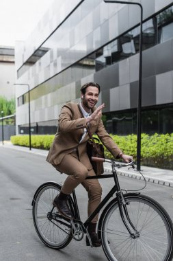 full length of cheerful businessman in earphones riding bicycle and waving hand near building and plants