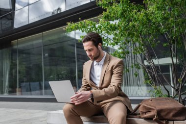 businessman in earphones using laptop while sitting on bench