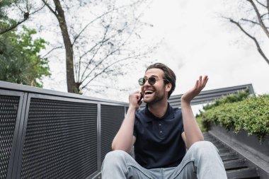 Güneş gözlüklü ve polo tişörtlü gülümseyen adam dışarıda cep telefonuyla konuşuyor.