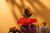 veselý středního věku africký Američan žena prodej ovoce a držení ventilátor na oranžové