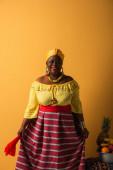 středního věku africký Američan žena v jasném oblečení a turban stojící v blízkosti ovoce v kovové míse na žluté