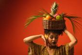 mladá africká americká žena s rukou v blízkosti obličeje držící koš s exotickým ovocem na hlavě na červené