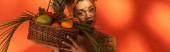 mladá africká americká žena držící koš s exotickým ovocem blízko obličeje na pomeranči, prapor