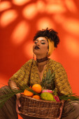 sebevědomý mladý afroameričan žena držení koš s exotickým ovocem na oranžové