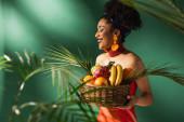 usmívající se mladá africká americká žena v červených plavkách drží koš s exotickým ovocem na zelené