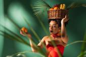 mladá africká americká žena drží pomeranč a koš s exotickým ovocem na hlavě za rozmazané palmové listy na zelené