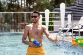 veselý arabský muž drží vodní pistole v bazénu