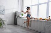 plná délka veselá mladá žena skákání v blízkosti ovoce v kuchyni